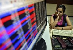 An investor watches the share index at a local share and stock market in the northern Indian city of Chandigarh