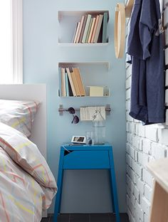 ENUDDEN Wall shelf $7.90  Bright blue IKEA bedside table. Above it a rail and two small book shelves.