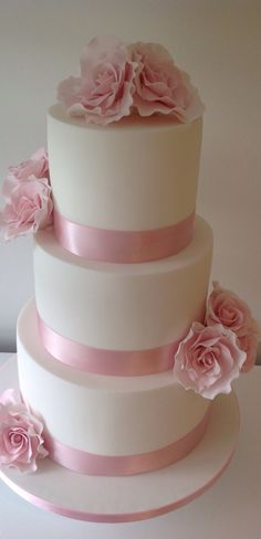 Pastel pink and white, 3 tier wedding cake with roses.