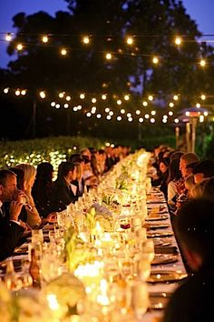 Long tables, lights in bushes and strung across above, and low candle light on tables = beautiful