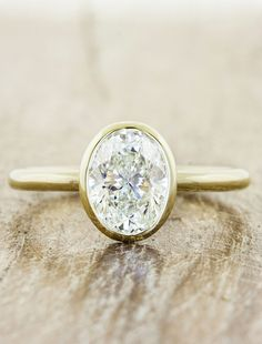 This minimal and modernist ring is created with recycled metals and a bezel-set center diamond. Also shown with other center stones.