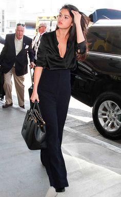 Selena Gomez usa blusa de seda e calça pantalona preta