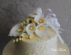 White almond wedding cake with raspberry filling iced in buttercream with piped buttercream scrolls. Gumpaste cala lily and freesia bouquet.