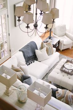 Living Room with white linen sectional, blue, gray and neutral accents, driftwood-like sofa table and tufted ottoman - Neutral Home Tour - Life On Virginia Street