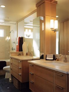 This master bathroom boasts a pair of modern vanities accented with sleek drawer pulls, contemporary faucets and sconces. Oversized mirrors bounce light around the space, making it feel twice as large.