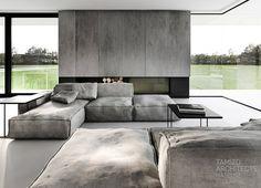 habillage de cheminée aspect béton, canapé rembourré et modulable en gris et table basse noire dans le salon