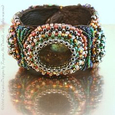 "Beautiful, One of a Kind bead embroidered cuff Bracelet; appropriately named ""Smoke and Mirrors"".  The center stone is a Labradorite cabachon and on either side is a light green rhinestone, all three are captured by seed beads and crystals. This is a really gorgeous Bracelet and makes a big statement! It measures 8-inches from end to end, but it is forgiving and does have some give as the leather is very supple. Each bead and crystal on this piece is literally touched at least 3 times to be…"