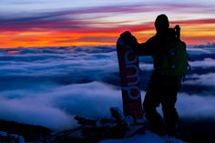 Justin Norman watches the sun go down after back country snowboarding at Crater Lake, National Park, Oregon