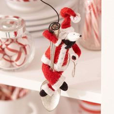Create an ornament featuring an adorable mouse dressed as Santa Claus. Made from fabric, wire, and a spoon, this fun Christmas craft will add Christmas cheer to any room.