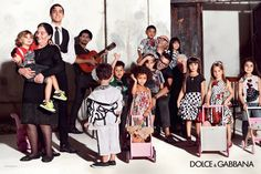 Domenico Dolce and Stefano Gabbana are portrayed together with a group of children in the Spring Summer 2015 children's wear advertising campaign