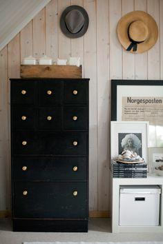 Brass drawer knobs pop against the black dresser in this Norwegian home.