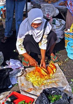 A vendor chops up some exotic produce at a street market near Borobudur, Indonesia