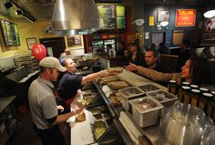 Potbelly Sandwich Shop employees Lance O'Hara and Kate Kleinheider serve customers during the restaurant's opening day on Tuesday in Campustown. Potbelly, known for its toasted sandwiches, signature shakes and live music, has more than 300 shops across the country, but the Ames location is its first in Iowa. Photo by Nirmalendu Majumdar/Ames Tribune  http://amestrib.com/news/pilot-potbelly-shop