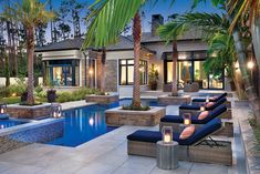 A warm and welcoming courtyard patio sets the tone, where wicker chaises recline poolside and soft light flickers from Z Gallerie lanterns as shadows dance across the water shimmering with UMI's mosaic glass tile. Neutral stone finishes, cool blue accents, and even the palm trees were meticulously selected so the home feels rooted in its lush Gulf Coast setting.