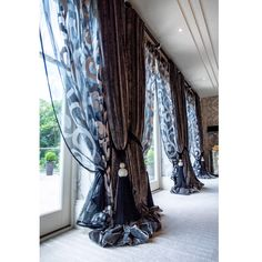 Double pair of curtains in contrasting fabrics, tied back with a pair of tiebacks