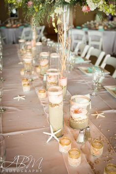 Beach themed wedding centerpieces (garden roses on top of sand and crushed seashells). Very beautiful but not over the top and cluttered.