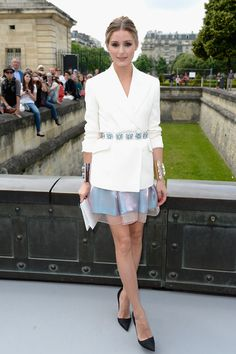 Olivia Palermo wearing a white blazer, blue skirt, double cuffs and black pumps at Dior.