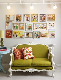 A chartreuse couch adds a pop of energy. green couch. happy colours, they make me smile. fun paintings on the wall. and a little blue side table.
