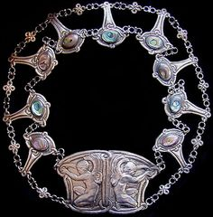 This is not contemporary - image from a gallery of vintage and/or antique objects. BERTHA L. GOFF  A silver belt with a twin panel buckle depicting winged cherubs.  The drop shaped links of the belt set abalone.