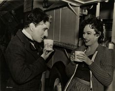 """Charlie Chaplin and Paulette Goddard (in costume as Hannah) take a break, during production of""""The Great Dictator"""" 1940."""