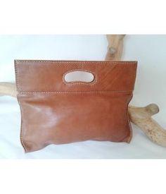 Lederen handtas, hazelnootkleurig.Handgemaakt, voorzien van contrasterend stiksel.Binnenzijde gevoerd met een katoenen batik en voorzien van vaktje met rits.Afsluitbaar met ritsHeerlijk soepel rundleer.Afmetingen: 37x31 cm. (bxh), voorzien van kleine...