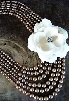 6 strand champagne pearl necklace.White fabric flower with vintage rhinestone in the center.