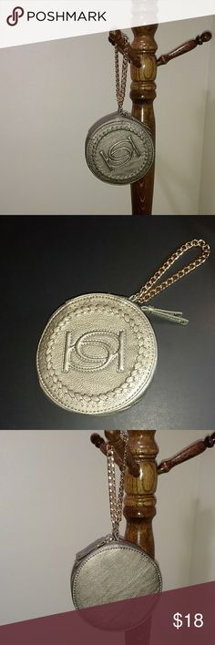 BEBE GIA WRISTLET Cute round pewter color wristlet with zip around with  closure. Outside front has SIgnature BB logo and a beautiful decorative finish around the edge. Content: shell is 100% Polyurethane & Lining is 100% Polyester.  Goldtone hardware with a shiny gold tone wrist chain. Interior lining  looks like satin in a pewter color with a BeBe name plate in leather like material. Preowned & never used. Looks like new inside & outside. From a smoke free home. BeBe Bags Clutches…