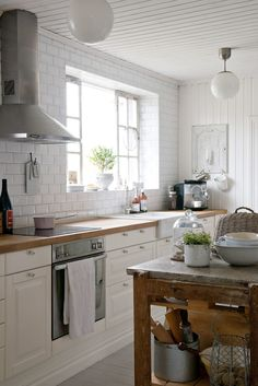 love the white tiles and silver range hood.  white windows and wood countertop w/rustic table.