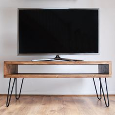 Handmade Solid Wood Box TV Stand with Steel Hairpin Legs – Dark Wood Finish  Style: A vintage retro wooden Box TV Stand in a dark wood finish with mid-century style metal hairpin legs in a choice of black powder coating or bare steel (clear coated).  Wood Characteristics: Our furniture grade solid wood is beautifully crafted to retain the natural features of the wood including original knots and grain. Every coffee table is unique and reflects a rustic finishing style. We love our wood this…