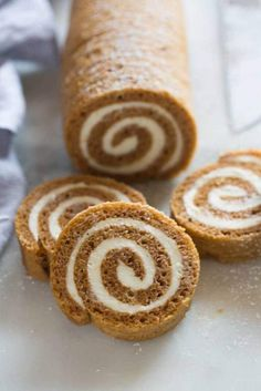 A pumpkin roll laying vertically with four slices of pumpkin roll laying in front of it.