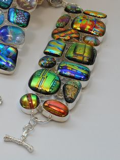 "This vibrant handmade artisan Dichroic Glass bracelet has amazing three-dimensional color in each original silica stone, set in 925-hallmarked sterling silver. Length: 6.5-8"" Adjustable toggle clasp. Widest center dimension: 1.5"""