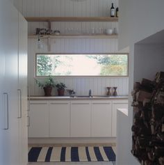 long window; textured white surround; mixed w/ green plant-life; timber shelving; white cupboards. Overall - similar idea (smaller scale)
