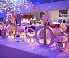 A couple of circular vases are paired with romantic gold votives and floating candles.