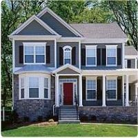 Grey house, brick accents, navy shutters, white trim, & red door