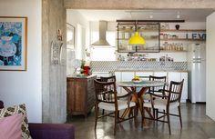 Sala de jantar integrada à cozinha com mesa redonda, pendente amarelo e armários abertos.