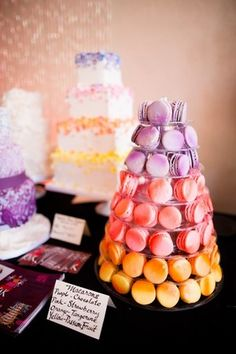 Macaron towers: A colorful wedding dessert table inclues an ombre pink and lilac macaron tower and a white square wedding cake decorated with ombre flower petals. | SoHo63 in Chandler, AZ