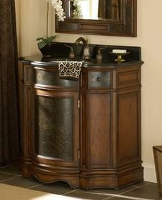 The Doucette sink chest has acid etched door and drawer fronts and a mahogany finish. Complete with a black granite top, two drawers and storage cabinet underneath.    www.mkhomedesign.com