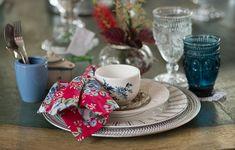 A mesa foi montada com sousplat e louças misturadas (geométricas, florais e brancas com relevo). No lugar do pires, um porta-copos prateado. Na composição há, também, uma minichaleira para escolher o sabor do chá a granel