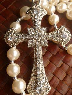 Terço de pérolas importadas de 10mm e intermediárias 12mm. Com crucifixo de strass prateado de 8 cm e o terço todo tem 48 cm R$ 100,00