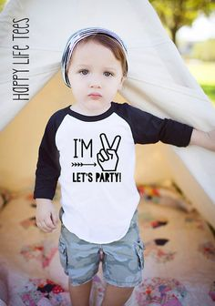 """Your little boy is turning two years old! Let him celebrate in style with this playful and funny t-shirt created just for him. Featuring the phrase, """"I'm 2, let's party!"""" your little one will be stylish in one of our cozy tees. This black and white graphic tee will surely be the life of the party. Whether you are dressing your baby for a big family party or simply having an intimate celebration at home, this adorable tee will make your day. Each cozy tee is Super Soft American Apparel Poly…"""
