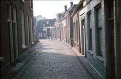 """Het Schalderoi gezien vanaf de Grotestraat, richting de Willemsgang. Bij de lantaarnpaal, destijds een ontmoetingsplaats voor de mannen uit de buurt, ging je rechtsaf de Willemsgang in, richting Boddenstraat. Op de hoek stond het winkeltje van Borrink, begonnen als kruidenier en daarna o.a. handelde in tabaksartikelen. In het huisje rechts ernaast, op nummer 9, groeide Leidy Wohlgemuth-Rooze op, schrijfster van de inmiddels vierdelige boekjesserie """"Schalderoi, hart van Almelo"""". In het witte…"""