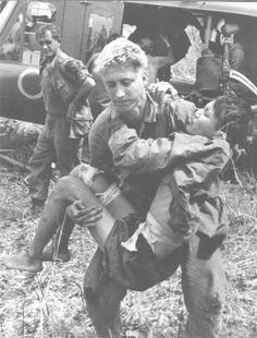 An American medic lifts a wounded Viet Cong POW.