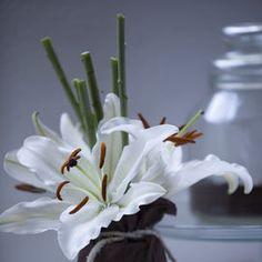 Un vasetto di vetro (per esempio quello di sottaceti) e un sacchettino di tela da legare con un filo di rafia o un nastro di seta: un centrotavola di fiori per rallegrare con semplicità la tavola.