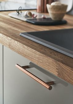 The copper handle complements the soft grey gloss of the kitchen cabinet doors.  Take a look at Howdens.