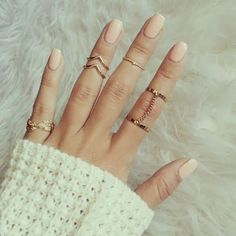 Nude nails and rings galore: LOVE. Bonus points for the sheepskin rug, too.