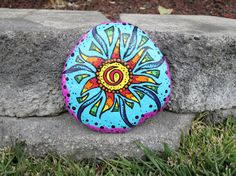 Painted Beach Rock, Sun, Stylized, Abstract, Rainbow Colors. Use cheap brushes, patio paint (works well with rocks and terracotta), and seal it.