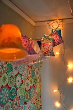 Lamp shades on a string of lights. Plastic cups covered with material. This is really cute and would be great in a bedroom or on a patio. I am definitely gonna try it.