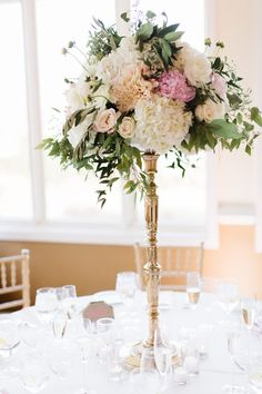Tall blush and gold centerpiece Peonies, dahlias, hydrangea, gold pedestal, greenery, roses.  -Florals by Jenny  -Jana Williams Photography -Me Weddings and Events