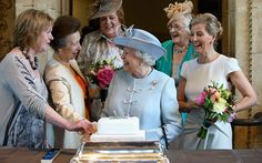 Countess of Wessex and the Princess Royal look on as Queen Elizabeth II cuts a Women's Institute Celebrating 100 Years cake at the Centenary Annual Meeting of The National Federation Of Women's Institute at the Royal Albert Hall, London