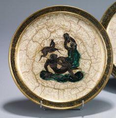 Jean Mayodon (1893-1967)  Assiette en céramique décorée d'un couple assis et d'une biche, émaillé noir et vert sur fond ivoire craquelé or. La bordure à galon gris et or, le revers vert antique Signature monogramme à l'or, datée 1950 et située Sèvres